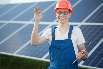 Worker on solar power station. Young man smailing, showing ok with his fingers, solar panels behind him.