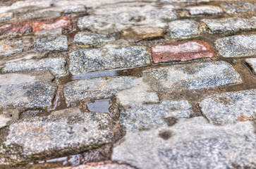 Macro closeup of wet, puddles and cobblestone street rocks with colorful texture and detail