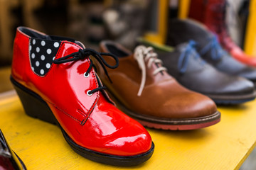 Macro closeup of vintage shoe display at store with bright red vibrant heel