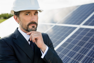 Portrait of client in white helmet at solar power station. Man in business suit holding hand to his chin.