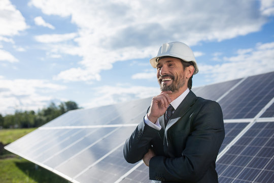 Man in business suit happily smailing, solar panels on backstage. Client in white helmet standing at solar energy power station.