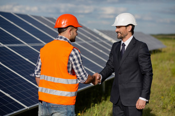 Businessman and foreman shaking hands at solar energy station. Solar panels in the field, two men making agreement.