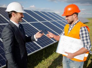 Business client stretching out photovoltaic item to foreman. Solar station in the open air, client and worker discussing technical details.