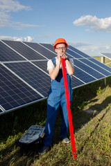 Worker with scale, solar panels behind him. Man in blue overall with tool at solar energy station in the field.