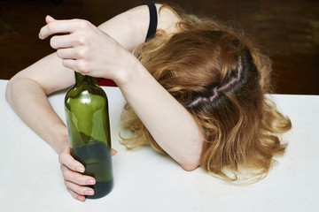 Drunk woman with bottle of wine, asleep at the table.Women's alcohol dependence.