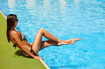Back of beautiful elegant tanned woman relaxing in bikini and sunglasses in swimming pool spa. Portrait in hot summer day and bright sunny light.