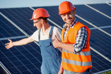 Foreman and employee at solar energy station. Foreman showing thumb up and looking in camera.