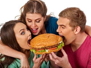 Hamburger fast food with ham and group people . Good Fast food concept. Friends man and two women eating sandwich junk in party. Girls fool around and feed man.