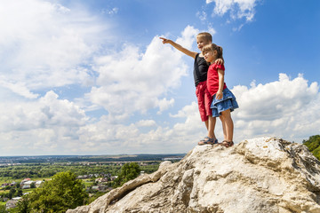 Little children boy and girl standing on mountain rock and looking ahead. Boy showing with his hand