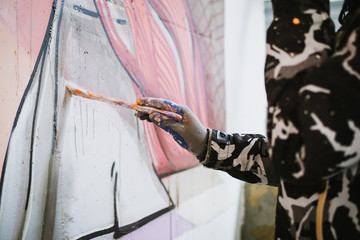 Graffiti artist painting with brush on the wall