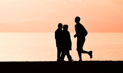 Old couple walking near the sea at sunset. A man running on the seashore, silhouette.