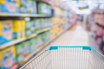 Shopping cart view in Supermarket aisle with diaper shelves