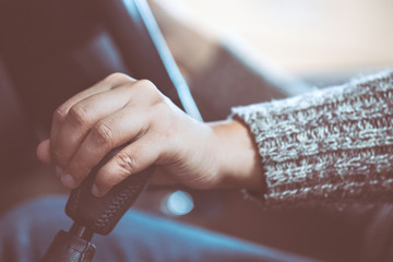 Woman hand shifting the gear stick while driving a car in vintage color tone