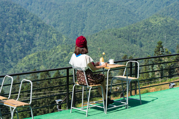 A girl drinking coffee in the morning in the mountains