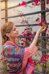 Young ethnic woman touching flowers in a garden