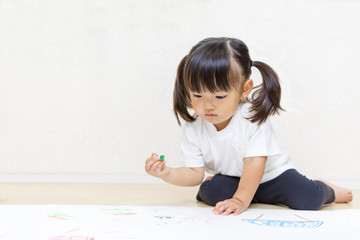 フローリングで絵を描く幼い女の子