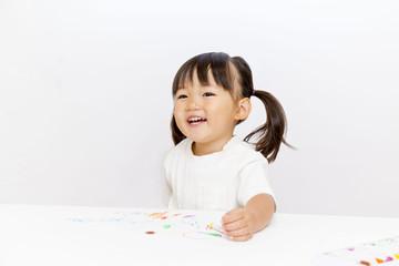 クレヨンで絵を描きながら微笑む幼い女の子