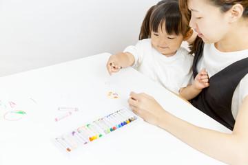 お母さんと一緒に絵を描く幼い女の子