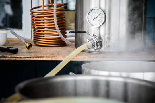 Home Brewing Kit and Pouring Craft Beer Wort into the Boil Kettle.