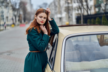 Beautiful young woman standing by her car outdoors in the city