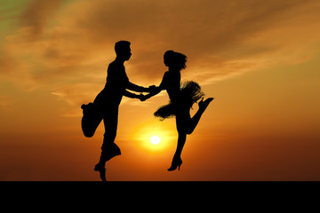 Silhouette couple in the active ballroom dance on sunset