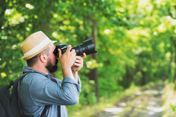 Male photographer with backpack and camera taking a photo. Travel Lifestyle hobby concept adventure active vacations outdoor