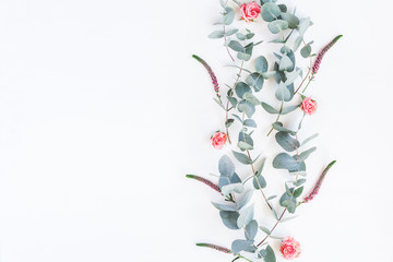 Flowers composition. Pattern made of rose flowers and eucalyptus branches on white background. Flat lay, top view, copy space