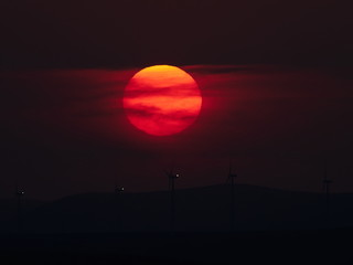 beautiful sunset with wind turbines on the hill in summer, silhouettes