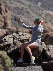 Young female traveler taking selfie on the beautiful rocky background in Teide Natural Park , Tenerife