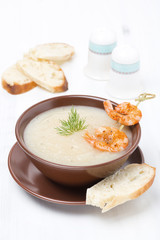 Potato cream soup with glazed shrimp and bread