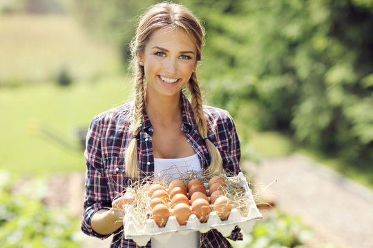Young woman with fresh organic eggs