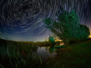 beautiful sky at night with startrails over the lake