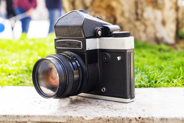 Vintage digital camera on boulder over blurred nature background. Shallow depth of field with focus on camera. Outdoor.