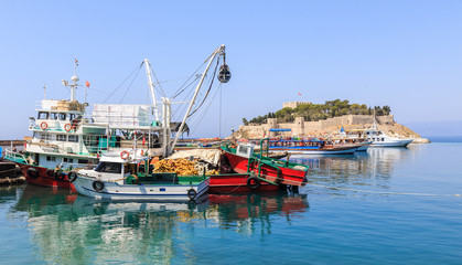 Fishing port in Kusadasi on the south coast of the Aegean Sea, Turkey. In background Guvercinada (literally: Pigeon Island) with castle and citadel