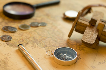 Compass ,coins and Wooden plane on world map, selective focus , vintage style.Travel and holiday concept.