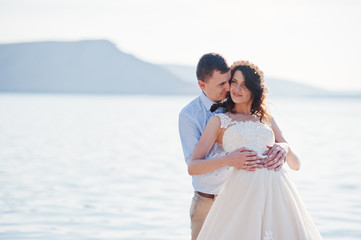 Amazing young couple holding hands on the lake shore on their sunny wedding day.