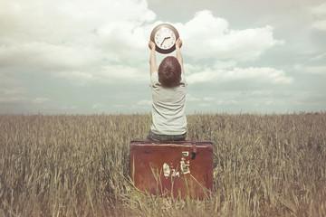 Little boy raises in the sky a watch in a surreal landscape
