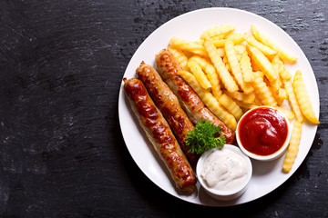 plate of grilled sausages with french fries