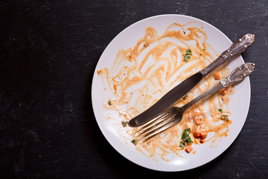 empty dirty plate on a dark background