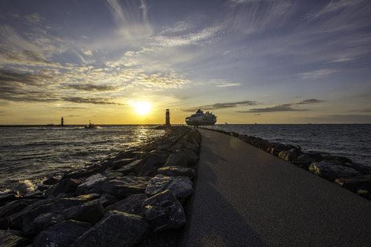 Kreuzfahrtschiff verlässt den Hafen von Warnemünde an der Ostsee im Sonnenuntergang