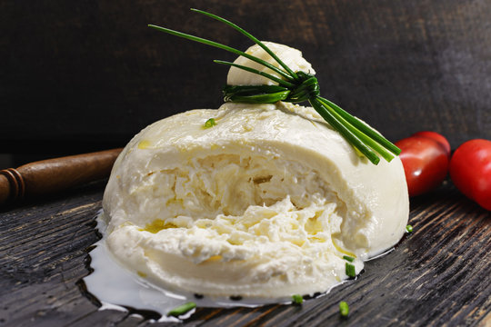 Burrata, fresh Italian cheese with tomatoes on a black wooden background.