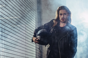 Stylish long haired bearded man in leather jacket holding helmet and looking at camera