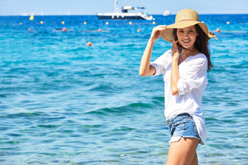 Happy girl in big hat stands in the sea on a sunny day