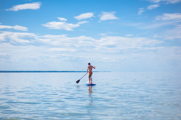 A young guy is floating on a sup board against the blue sky