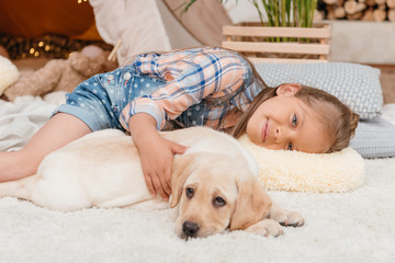 little caucasian girl and labrador puppy lying on floor together