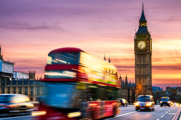 Big Ben with the Houses of Parliament and a red double-decker bus passing at dusk