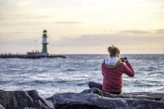 Junges Mädchen am Meer im Sonnenuntergang