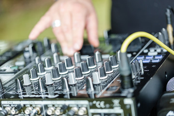 Dj works on mix console at outdoor party