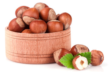 Hazelnuts with leaves in a wooden bowl isolated on white background