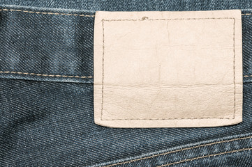 Denim jeans fabric texture background with blank leather label for beauty, fashion and clothing idea concept design.